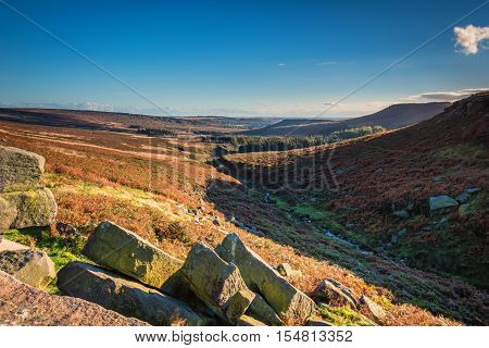 Burbage Brook and Higger Tor, the stream flowing down it's valley past the escarpment, in the Peak District National Park on a sunny day in autumn