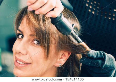Curling hair with curling iron, toned image, horizontal