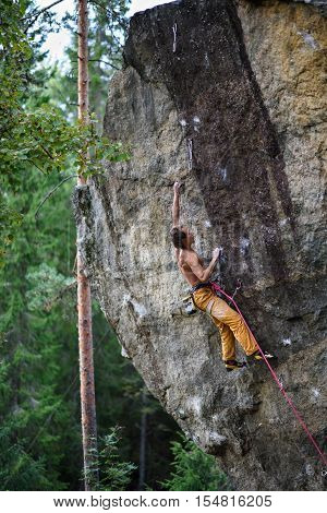 Climber on a cliff. Lead climbing on overhanging cliff.