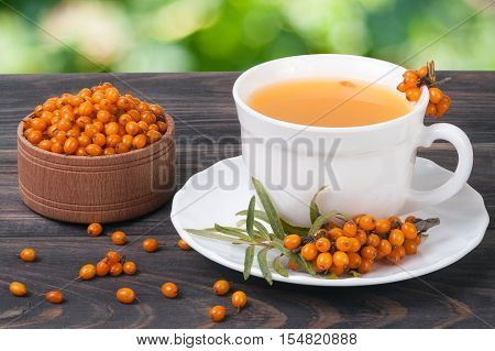 Tea of sea-buckthorn berries on wooden table with blurred garden background.