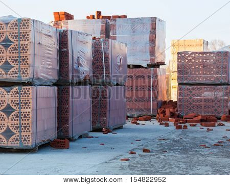 Stacks of silicate bricks on wooden pallets and in polyethylene