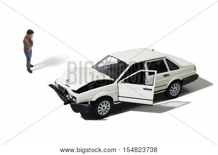 Toy Man Looking at Wrecked Model Automobile on White Background
