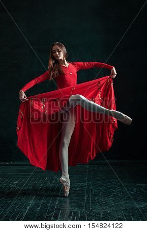 Ballerina in red dress posing in pointe shoes at black wooden pavilion