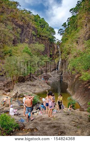 Koh Chang, Thailand - December 20, 2015: Realistic image of lots of tourists in the Khlong Phlu Waterfall Mu Koh Chang National Park. Unidentified people admiring the waterfall swim and take photos.