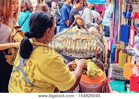 Bangkok, Thailand - December 22, 2015: Unidentified food vendor on the busy street of Chinatown district in Bangkok Thailand. Street cooking is a tradition and ubiquitous in Thailand.