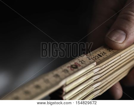 Close up wooden folding ruler with a hand