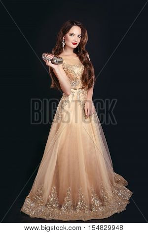 Fashionable Women Accessories. Beautiful Brunette Model Posing In Long Golden Dress With Gems Clutch