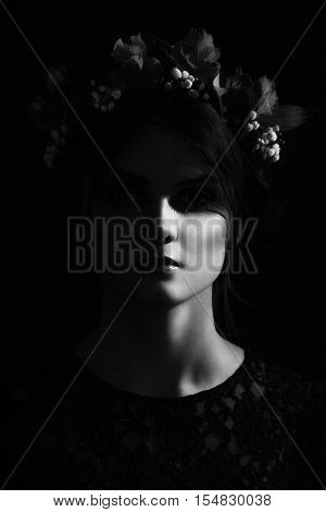 Creepy scary black-haired brunette woman with a rim of fresh flowers on her head in a black lace dress on black background, black and white photo