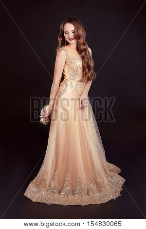 Attractive Brunette Woman In Golden Long Dress Isolated On Black Background. High Fashion Studio Pho