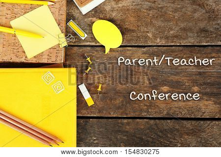 Stationary with text PARENT/TEACHER CONFERENCE on wooden background. School concept.