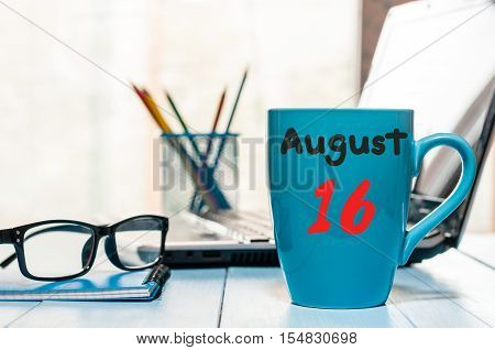 August 16th. Day 16 of month, morning coffee cup with calendar on office workplace background. Summer time. Empty space for text.