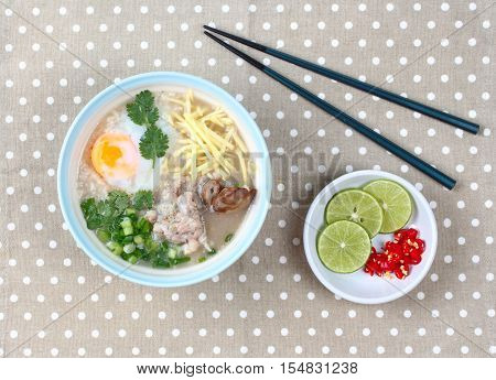 Home made,Rice porridge with mined pork and chicken lever served with spicy sour filling is popular food set of Asia .