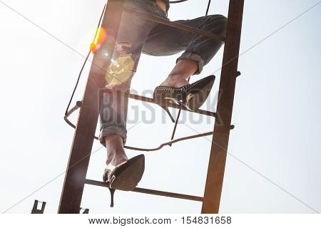 Woman in stiletto-heeled shoes climbing the metal industrial ladder.