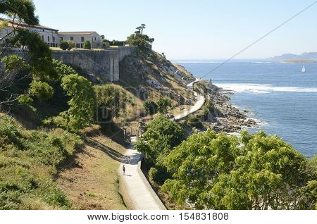 BAYONA, SPAIN - AUGUST 7, 2016: Promenade next to the fortress of Monterreal in Ria of Vigo in Bayona Galicia Spain.