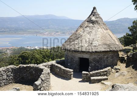 Prehistoric reconstructed house in the remains of a celtic settlement in Santa Tecla Mountain with views to Minho estuary in Galicia Spain.