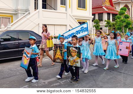 Bangkok, Thailand - January 8, 2016: Pupils of the school holds the flag of Thailand portrait of Buddha and Thai King Bhumibol Adulyadej during the procession. The king is highly revered in Thailand.