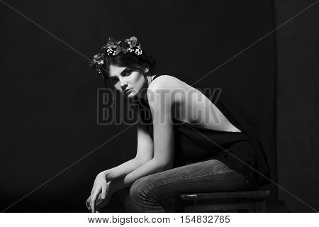 Beautiful sexy black-haired brunette woman with a rim of fresh flowers and petals on her head in a black t-shirt and jeans sitting wih hands on knees on black background.