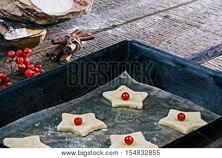Unbaked star-shaped christmas cookies on the baking tray.  Ingredients on the background