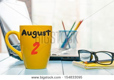 August 2nd. Day of the month 2, morning yellow coffee cup with calendar on business workplace background. Summer concept. Empty space for text.