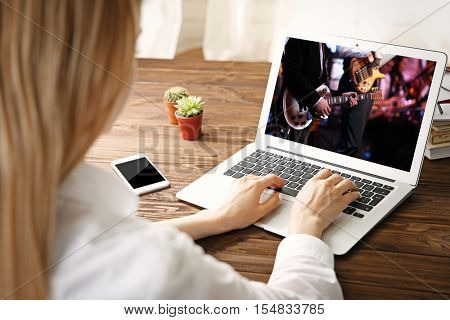 Woman watching musical performance online on laptop. Video call and chat concept.