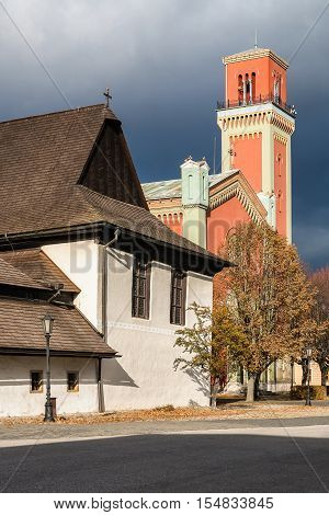Old Wooden articular church and New red protestant church in Kezmarok Spis region Slovakia. Old one is registered in UNESCO List of the World Cultural Heritage. Sunlight with dramatic storm clouds.