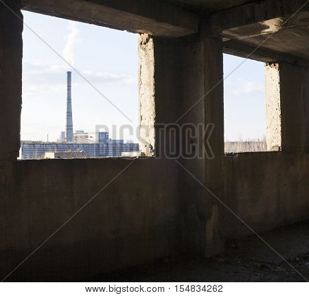 Industrial view from the window opening of the abandoned unfinished concrete building. Smoke stack of the power plant in the distance.