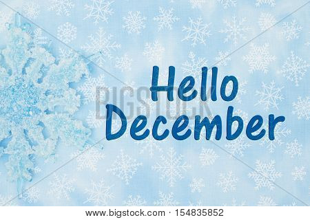 Hello December message A Snowflake with a blue and white snowflakes background with text Hello December