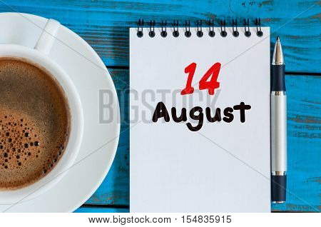 August 14th. Day 14 of month, loose-leaf calendar on blue background with morning coffee cup. Summer time. Unique top view.