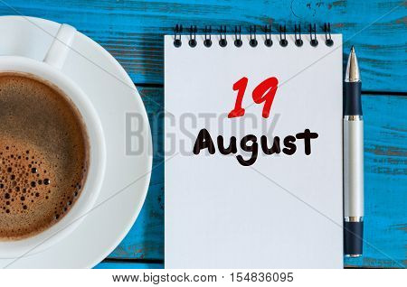 August 19th. Day 19 of month, loose-leaf calendar on blue background with morning coffee cup. Summer time. Top view.