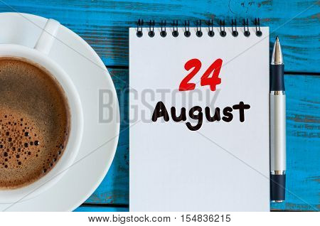 August 24th. Day 24 of month, loose-leaf calendar on blue background with morning coffee cup. Summer time. Top view.