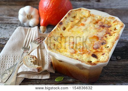 Vegetable pumpkin gratin with cheese in ceramic bakeware