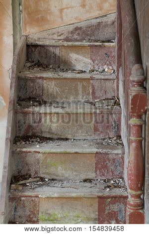 Vertical shot of a forgotten wooden stairway inside an empty abandoned house.