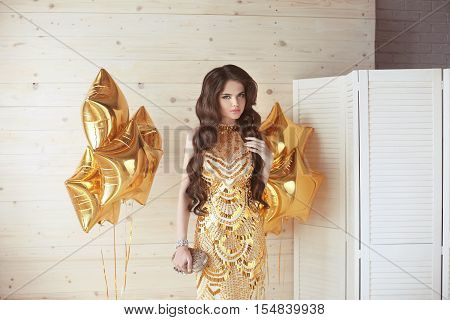 Beautiful Girl With Long Wavy Shiny Hair. Brunette Woman With Elegant Hairstyle In Golden Dress  Ove