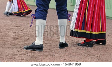Legs of man and woman who are dressed in traditional Estonian clothing. They look at dancing couple and are going to dance too.