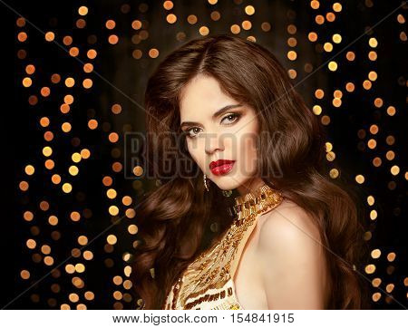 Beautiful Brunette Girl With Long Shiny Wavy Hair. Elegant Lady In Gold. Fashion Model With Curly Ha