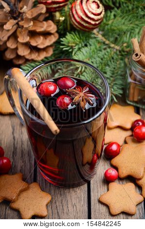 Christmas mulled wine. Holiday concept decorated with Fir branches, Gingerbread Cookies and Cranberries.