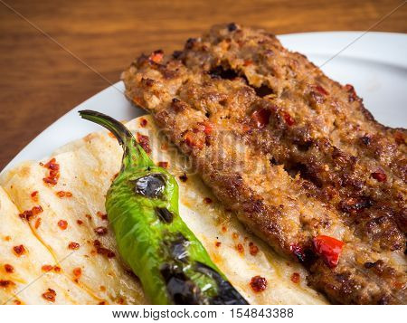 Adana Kebab served with green pepper and flat bread