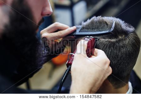 The Barber makes the man parted the customer an electric trimmer in a Barbershop