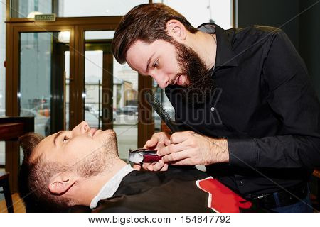The Barber man in the process of cutting the beard of client electric clippers in the barbershop