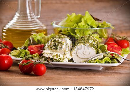 Goat cheese with salad and cherry tomatoes.