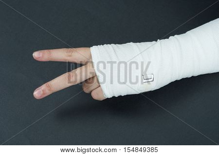 Hand Tied Elastic Bandage On A Black Background. Showing Two Fingers, Ok Sign Symbol.