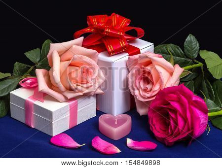 Gift Boxes with Bows Roses and Candle on a dark Background. For Valentine`s Day Bithday Wedding.