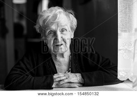 An elderly woman sitting at the table, black-and-white photo.