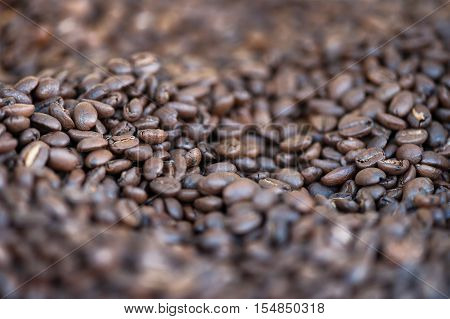 various roasted coffee beans in the foreground isolated