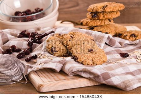 Oatmeal cookies with dried cranberries on wooden table.
