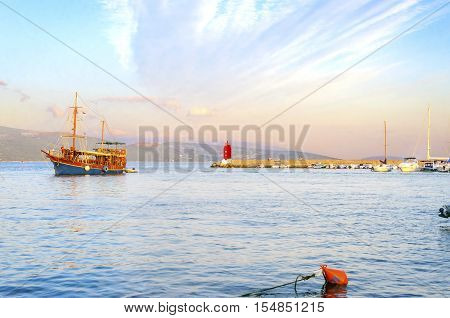 The red lighthouse mole at Krk town Croatia boats docked at the harbour pier and a sail boat entering at sunset. A small cylindrical tower at the biggest port of the island.