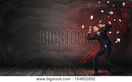Businessman protects himself from falling marks on his head on a background with red falling arrow. Recession and decline. Stock market plummet. Struggle and effort. Devaluation.