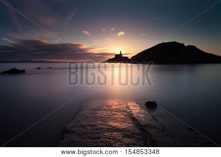 Daybreak at Mumbles lighthouse, an iconic structure in Swansea Bay, Swansea, South Wales