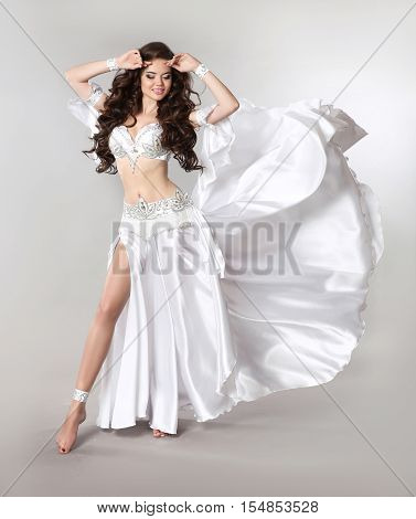 Bellydance. Beautiful Belly Dancer Woman In White Shining Costume With Blowing Fabric. Long Healthy