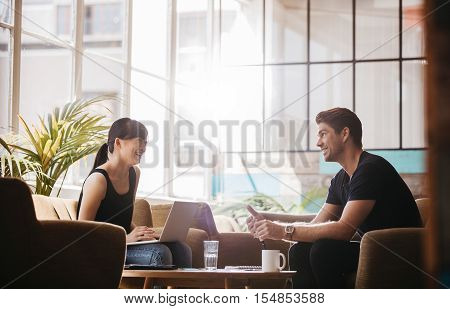 Shot of two people sitting in office lobby and working. Smiling business partners working together in modern office.